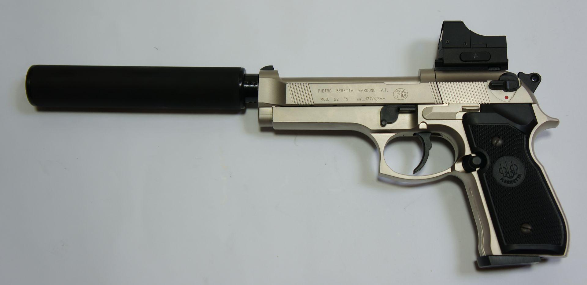 An so einer verchromten CO2 Pistole Beretta wird als Montagebeispiel gezeigt, dass als Zubehör hier auch  ein wirkungsvoller <a href=1165832.htm>Schalldämpfer mittels Adapter</a> passt. Optiken, wie <a href=../1130222.htm>das abgebildete Reflexvisier</a>, erfordern  <a href=../1130675-92.htm>eine passende Montageschiene</a>